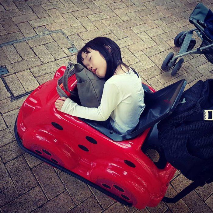 niña dormida en un carro de juguete