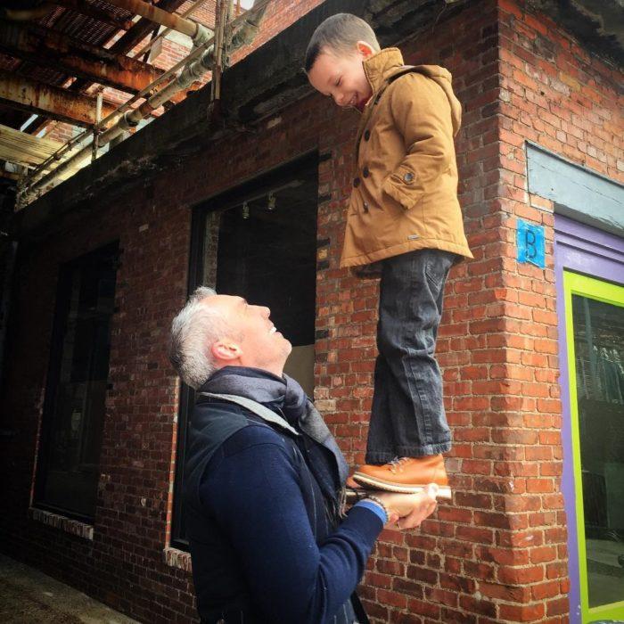 abuelo levanta en sus manos a su nieto