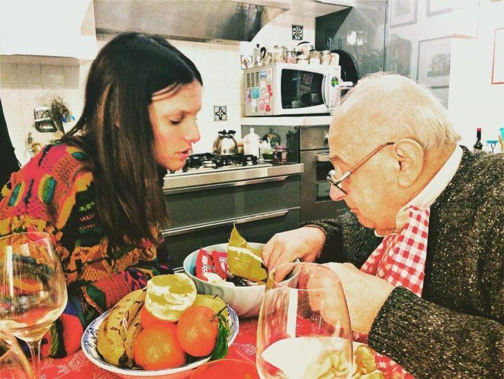 mujer dando de comer a su anciano padre