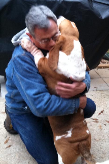 perro chiquito abrazando a hombre