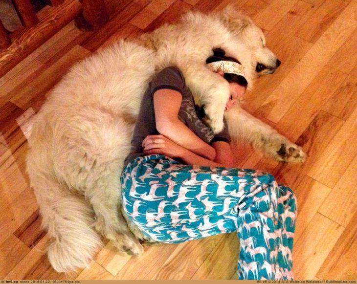 perro abrazando a su dueña mientras duermen