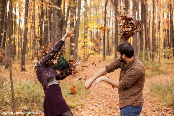 pareja aventándose hojas de arbol