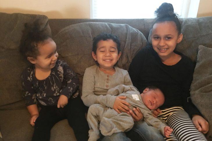 Hermanos con su hermanito recién nacido