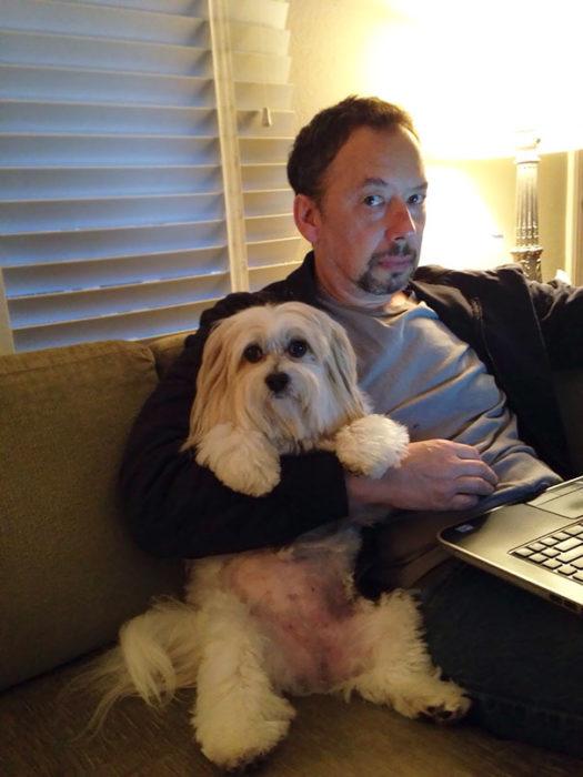 papa en la computadora abrazando al perro