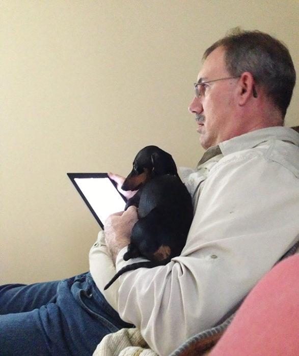papa con ipad en mano y perro en el otro