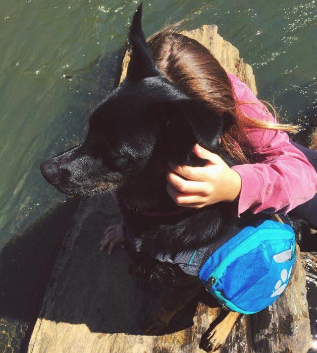 Chica abrazando a otra perrita negra