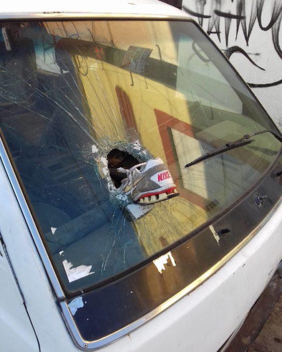 zapáto atravesó el vidrio de un coche