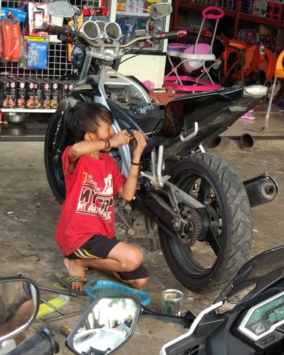 niño arreglando una moto