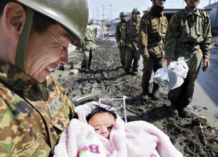 soldado sostiene a una bebé