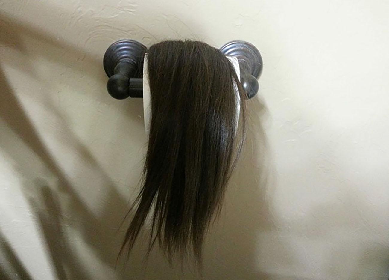 cabello enredado en rollo de papel de baño