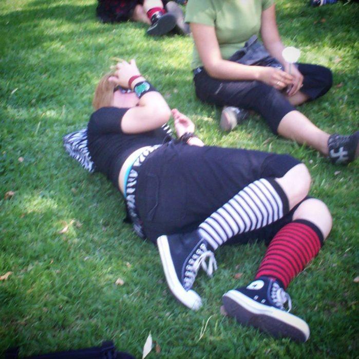 chica acostada sobre el pasto utiliza calcetines estilo emo