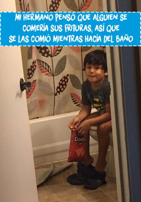 niño come sentado en la taza del baño