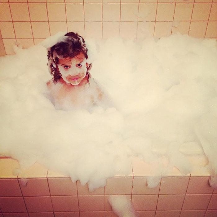 niña llena de espuma en un baño