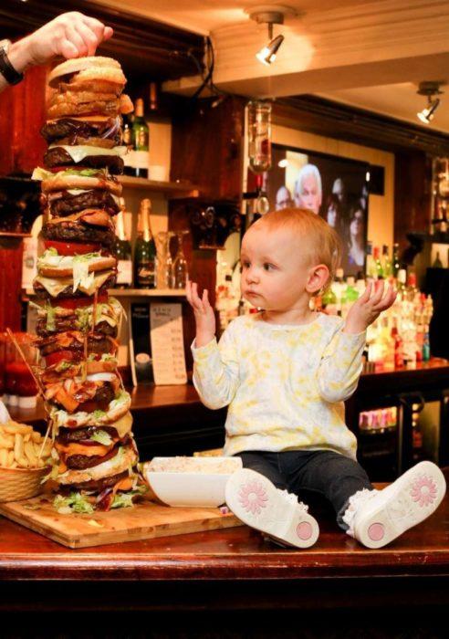 una niña junto a una hamburguesa enorme