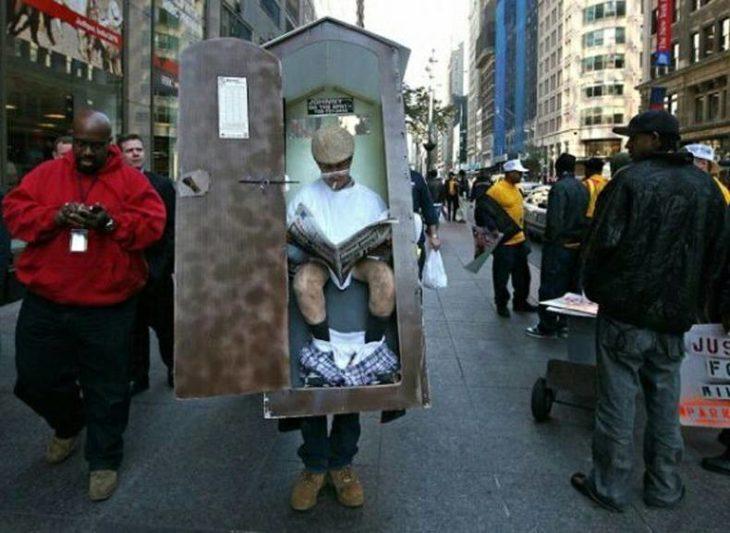 un hombre cargando una caja con la fotografías de un hombre en el baño