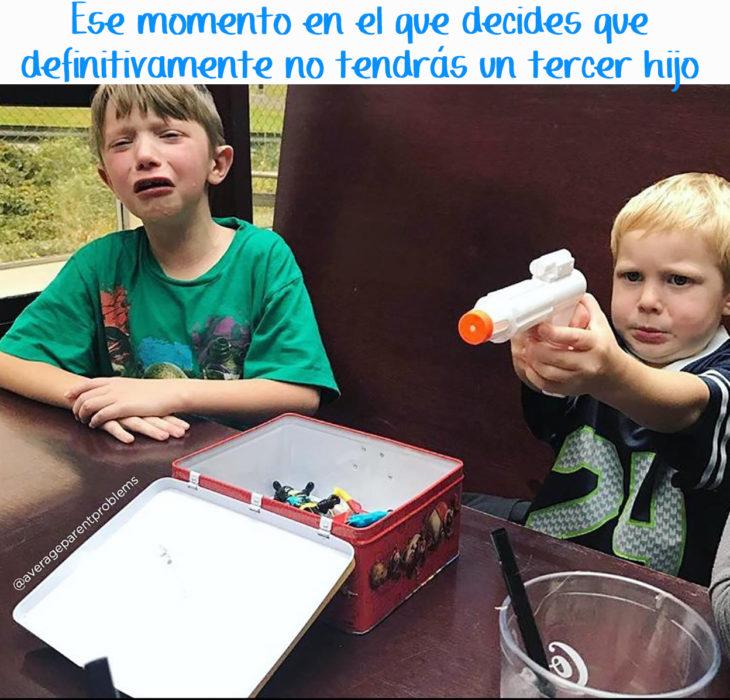 un niño juega con una pistola de agua mientras otro niño hace berrinche