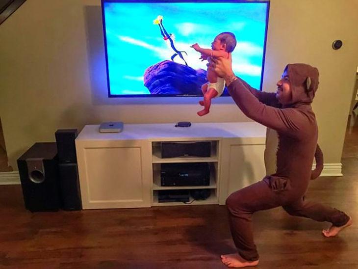 hombre vestido de mono sostiene a su hijo como en el rey león
