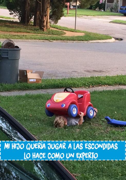 niño debajo de un carrito de juguete