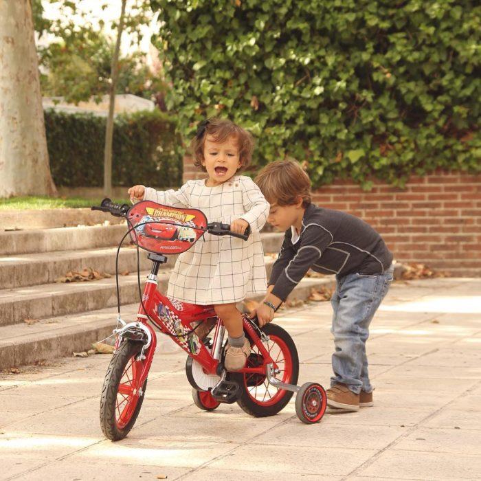 niño enseña a andar en bici a su hermanita
