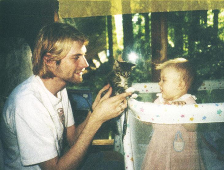 kurt cobain a los 26 años enseñándole un gato francés a su pequeña hija