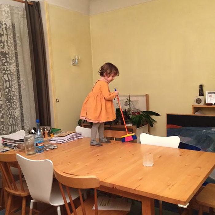 niña barriendo una mesa
