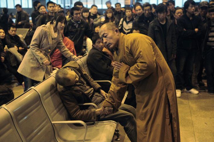 monje budista orando al lado de hombre muerto