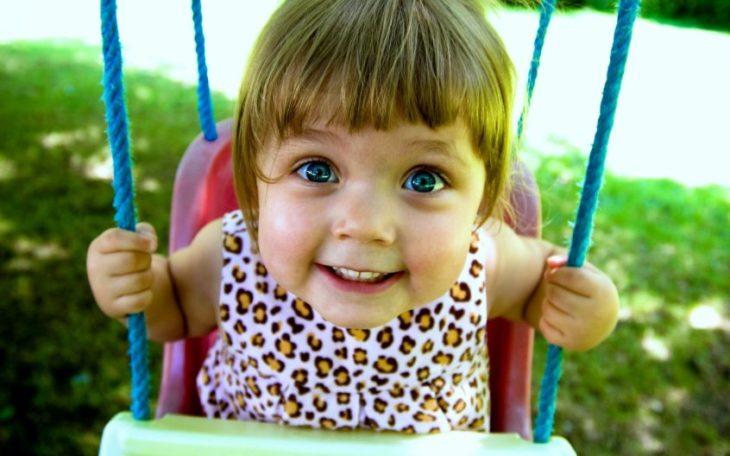 niña en un columpio sonriendo