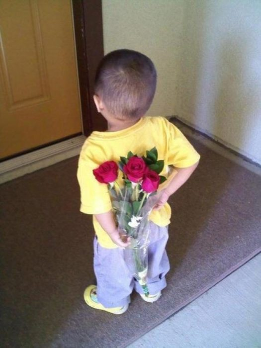 niño sostiene en la espalda un ramo de flores