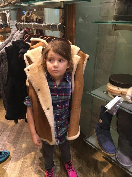 niña se pone un chaleco que sigue colgado