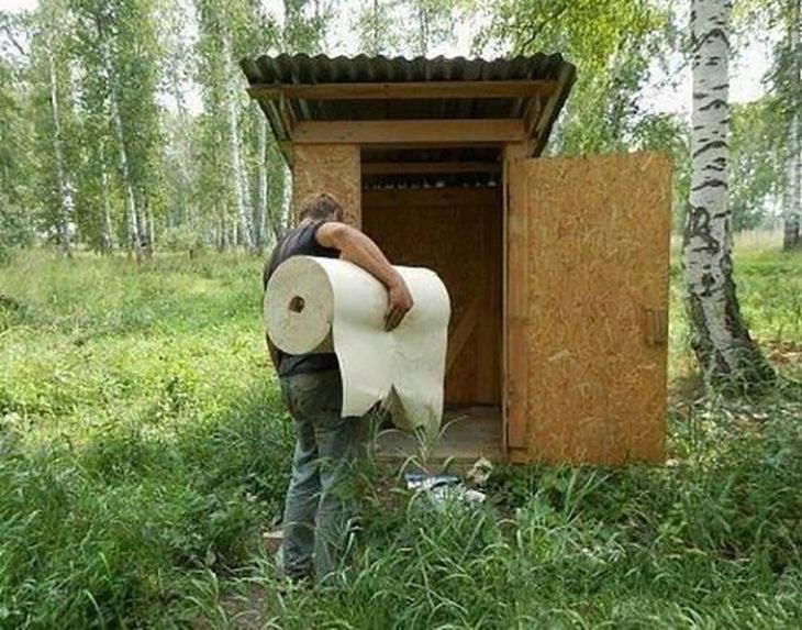 hombre cargando un enorme rollo de papel a un baño público