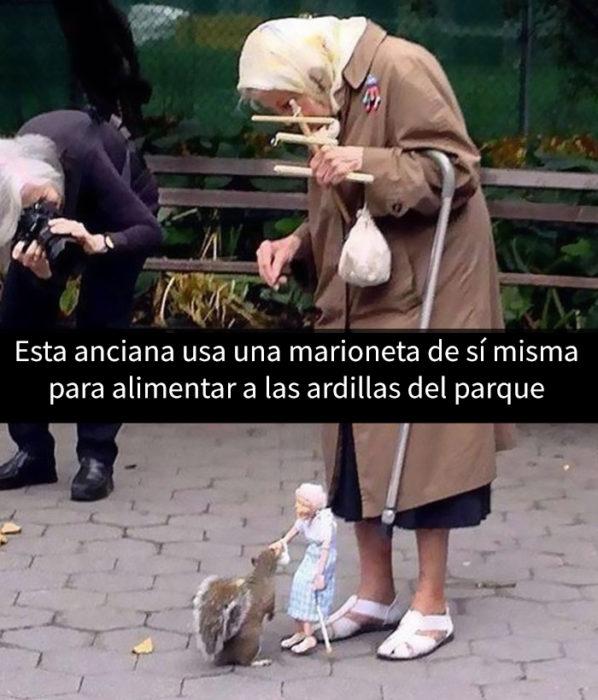 una anciana dando de comer a las ardillas con una marioneta de ella misma