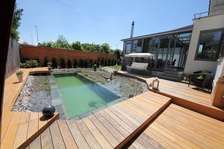 baldosas de madera rodean estanque de patio trasero de casa