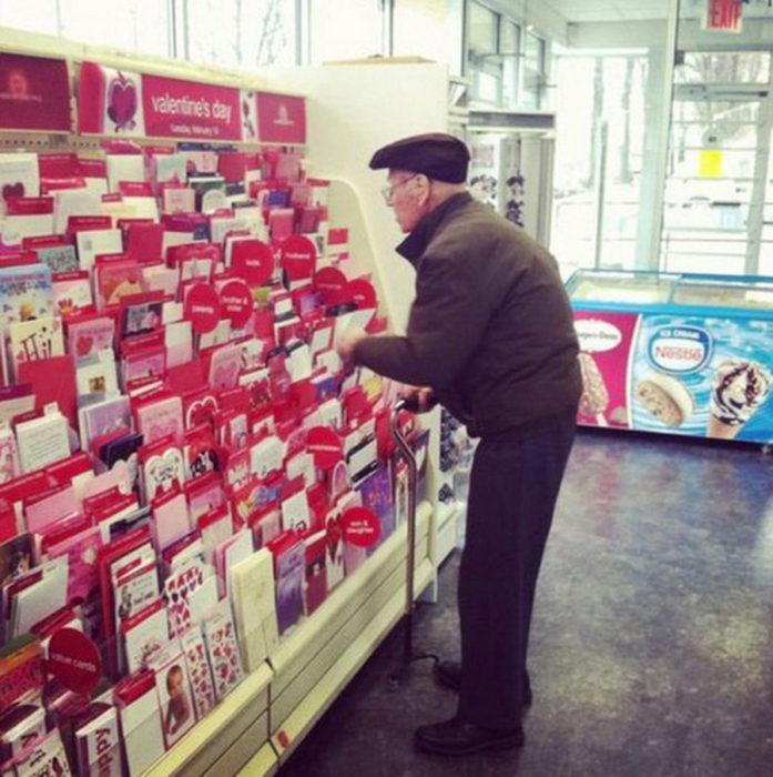Señor mayor escogiendo una tarjeta de san valentin