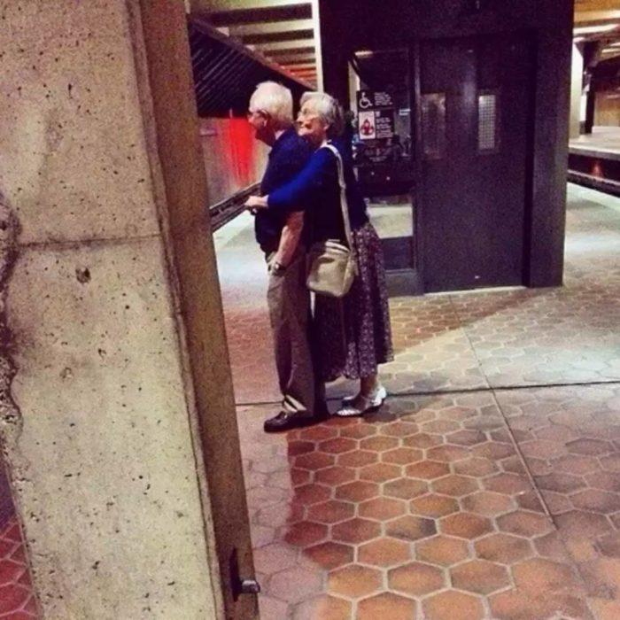 Pareja adultos mayores abrazados esperando el metro