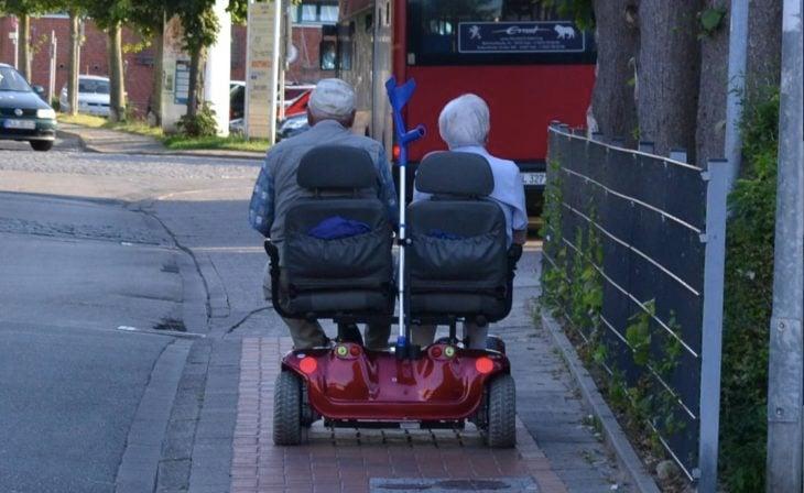 Pareja mayor paseando en sillas de rueda automáticas