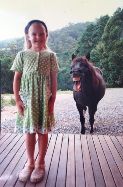 foto de niña y atrás un caballo sonriendo