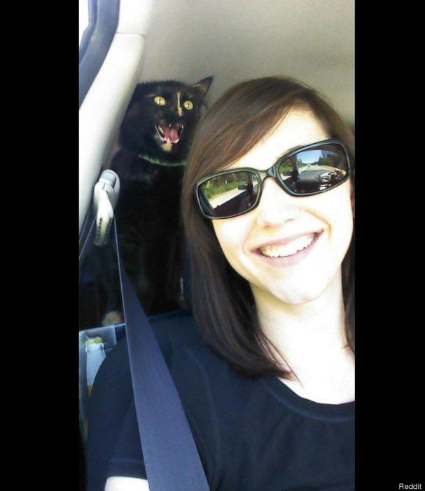 selfie chica y gato negro atrás