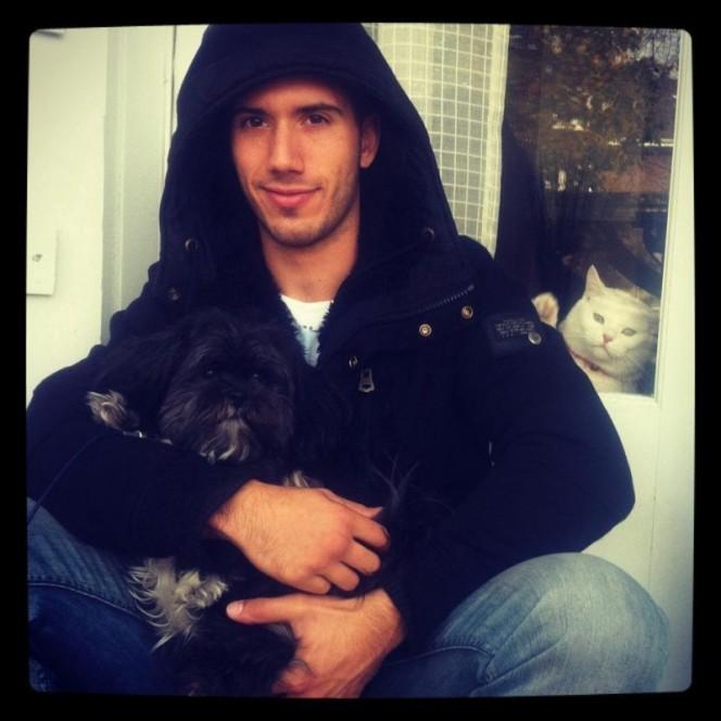 foto de joven con su perro y atrás se ve un gato