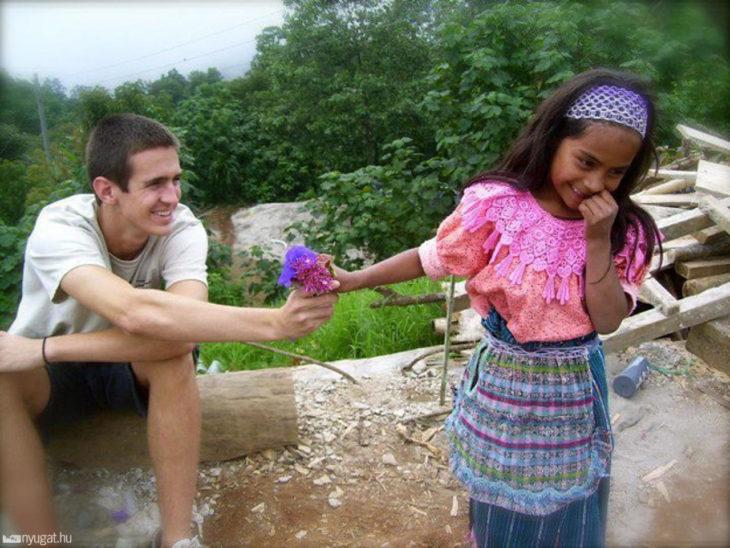 foto de turista que le da una flor a niña