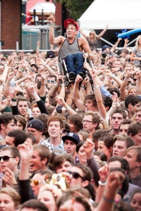 foto de concierto y todos levantan a chico en silla de ruedas