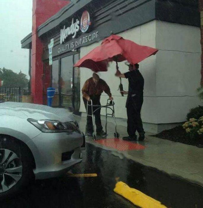 foto de trabajador de wendys que lleva una sombrilla tapando a un anciano de mojarse