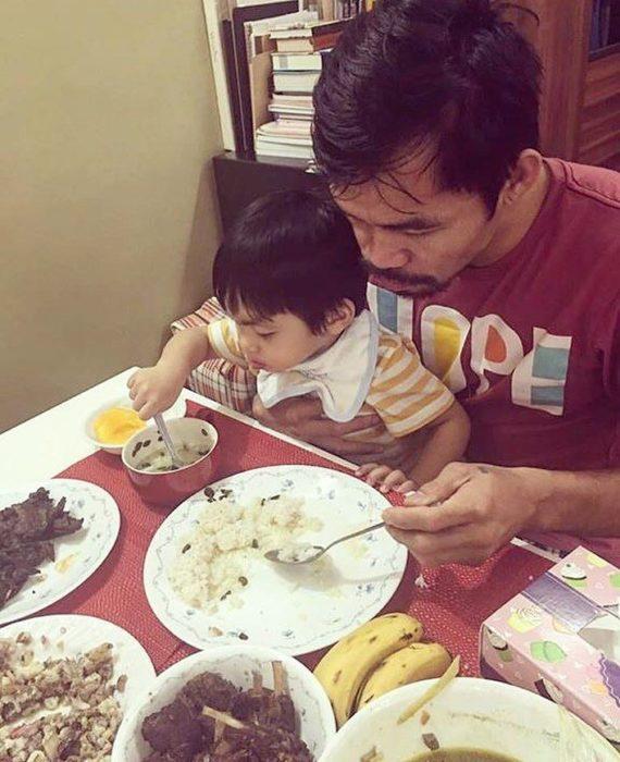 Manny Pacquiao comiendo con su hijo en brazos