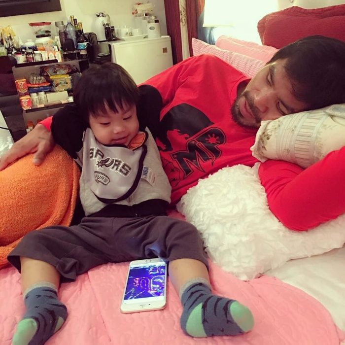 Manny Pacquiao y su hijo acostados viendo el celular