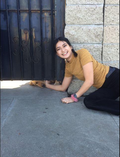 chica se toma foto mientras acaricia a perro por la rendija de un portón
