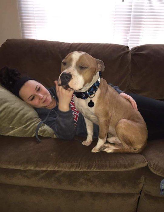 mujer acostada y perro sentado a su lado