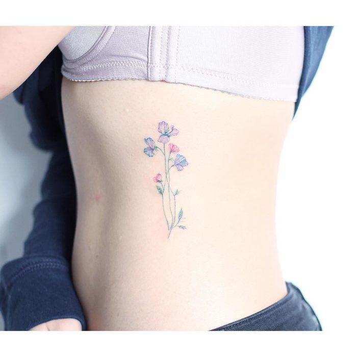 Tatuaje flores acuarela colores costillas