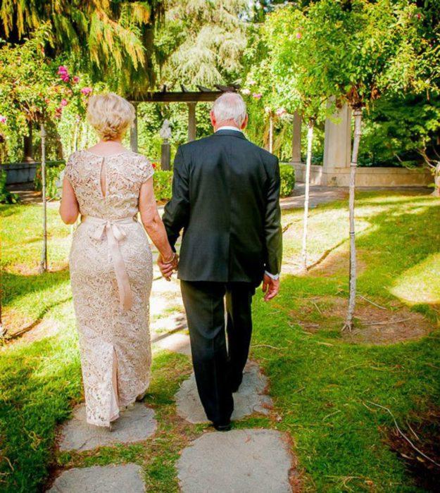 pareja de adultos mayores caminan por un jardín