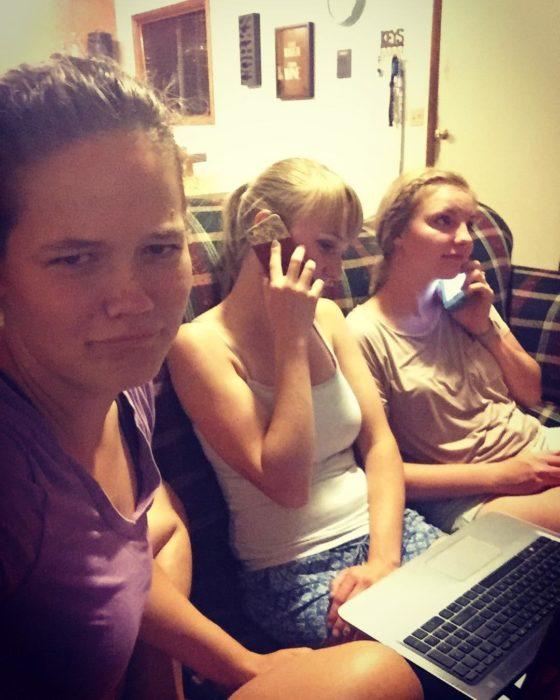 tres chicas en un sofá, dos de ellas están hablando por celular