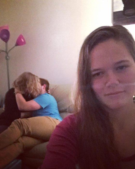 muchacha con cara seria frente a una pareja que se besa en un sillón