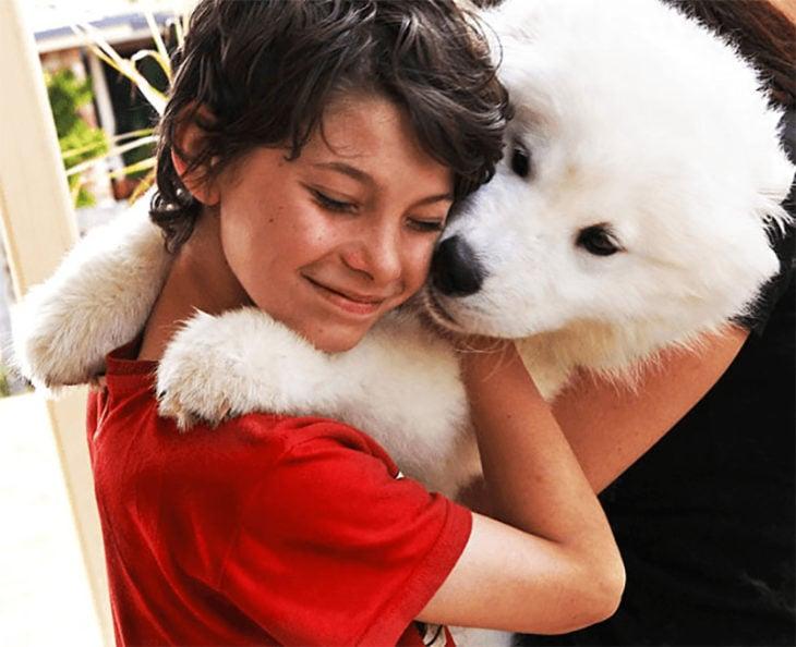abrazo perro pomerian blanco